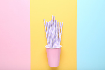 Pink paper cup with straws on colorful background