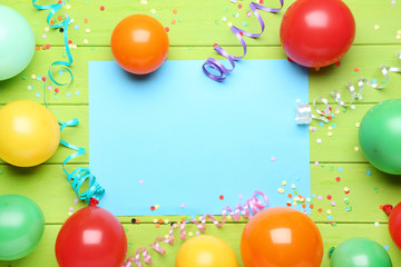 Colorful balloons with sheet of blank paper on green wooden table Wall mural