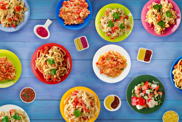 Pasta with vegetables and sauce on a table. Spaghetti on a plate. Mediterranean food.