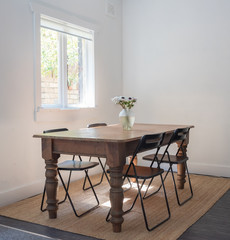 Full length view of rustic wooden dining table with four black chairs and vase of anemone flowers next to window with sunlight (selective focus)