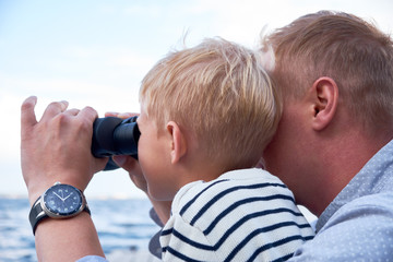 Close up portrait of boy and man sit at the deck and looks through binoculars
