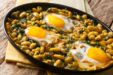 Tasty Iranian dish stew of beans and dill with fried eggs, garlic, turmeric close-up on a table. horizontal