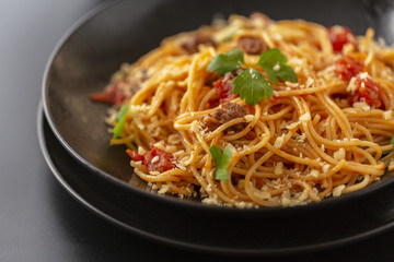 Delicious spaghetti with Bolognese sauce served on a black plate