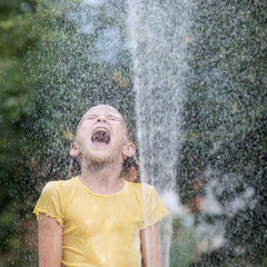 Happy little girl pouring water from a hose.