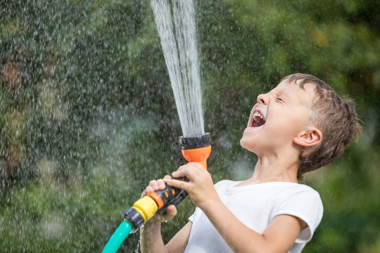 Happy little boy pouring water from a hose.