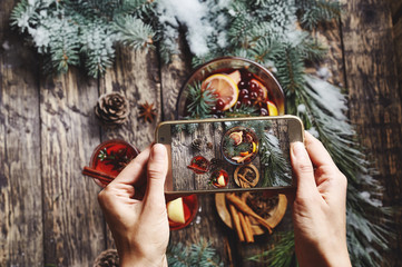 woman taking pictures of glass bowl with Christmas mulled wine on wooden background