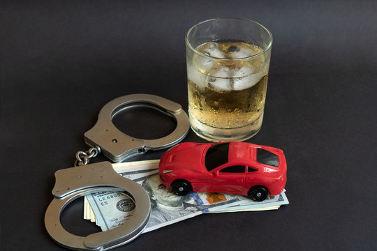 Alcohol, handcuffs and car toy on color background. Driving in a drunken state concept.