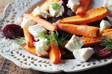 Healthy grilled beet, carrots salad with cheese feta, fennel on the rustic wooden table