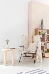 Armchair with pillow and blanket next to wooden table in bright living room interior. Real photo