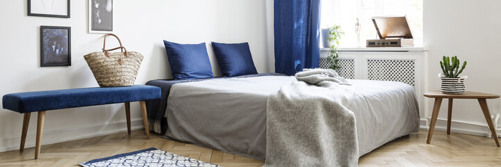 Real photo of a minimalistic bedroom interior with a bench next to a bed, wicker bag and pillows