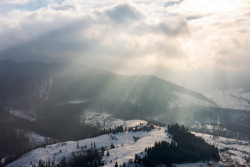 beams of light on winter morning. beautiful countryside with snowy hill