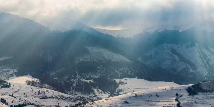 gorgeous panorama of mountains in winter. snowy hills lit with sun light through overcast sky. small village in the distant valley