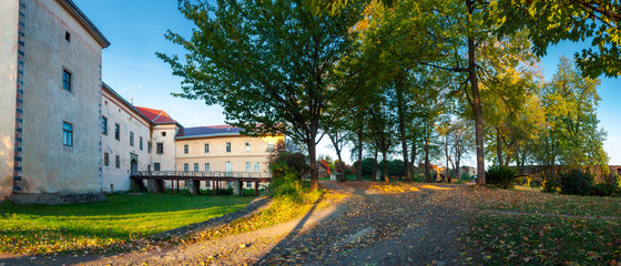 Uzhhorod, Ukraine - OCT 12, 2008: panorama of Uzhhorod castle inner courtyard. bridge and entrance to castle. beautiful park in evening light