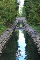 Old round stone bridge in the coniferous forest over a long narrow ditch with blue water between the stone walls in a beautiful city garden