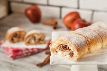 Apple strudel on a white square plate close-up and cut. Apple pie and red apples, cinnamon. Bright textural background with space for text