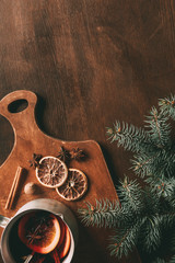 top view of hot homemade mulled wine with spices on cutting board on wooden background with fir branch