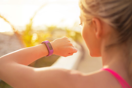 Fit girl using wearable tech during morning workout
