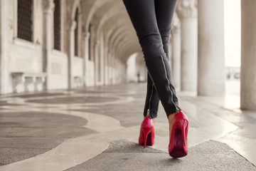Fototapeta Woman walking in black pants and red high heels obraz