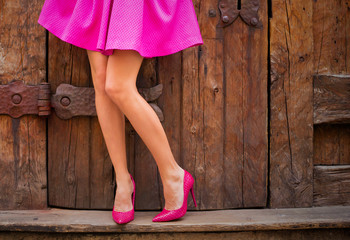 Woman wearing pink skirt and high heel shoes Wall mural