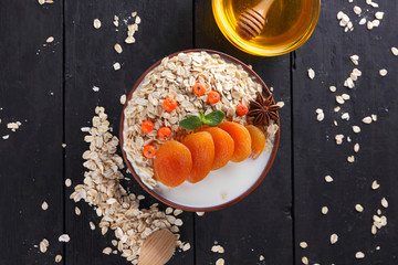 Oatmeal with dried apricots and honey on black background. Oat flakes with milk and green mint on dark wooden boards. Healthy food for vegans. Dry oats with berries of mountain ash. Autumn pattern