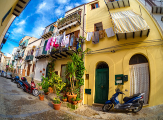 Traditional narrow street in the old town of Cefalu in Sicily, Italy
