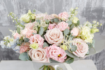 beautiful bouquet of mixed flowers into a vase on wooden table. the work of the florist at a flower shop. frosted plastic wrap