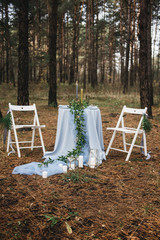 Decorated table with blue tablecloth, herbs, candles, Cutlery in anticipation of a romantic date in nature