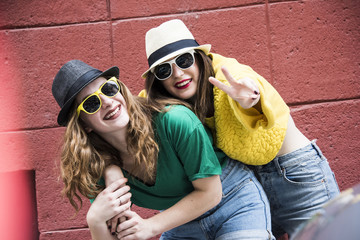 Two lovely hipster woman having fun in colorful outfits. Beauty and fashion conception.