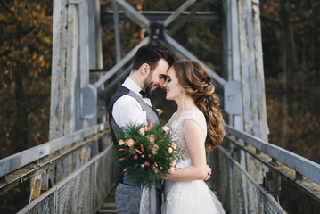 Happy young smiling bride and groom are standing on the suspension bridge. Wedding photos in an interesting place