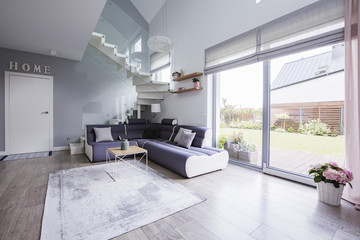 Window terrace, corner sofa, stairs and door in a living room interior. Real photo