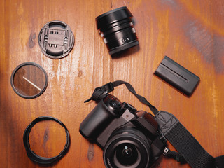 Top view of digital camera, battery, lens, cover, filter and parasol on wooden table. Equipment photographer concept