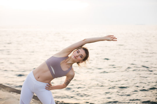 Nice girl in sporty top and white leggings dreamily looking in camera while practicing yoga with sea view on background. Young thoughtful woman stretching by the sea