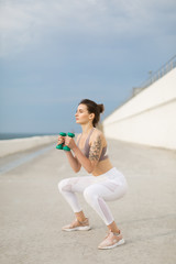 Young beautiful woman in sporty top and white leggings doing squats with dumbbells in hands while dreamily looking aside outdoor