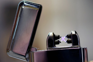Plasma arc lighter. Windproof, flameless and rechargeable electric lighter. Close up image with space for text.