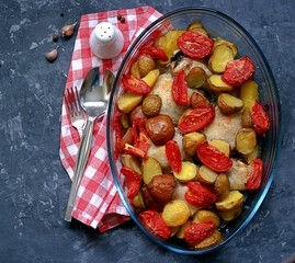 Baked chicken with potatoes and tomatoes in a glass form for baking on a dark gray background. Top view.