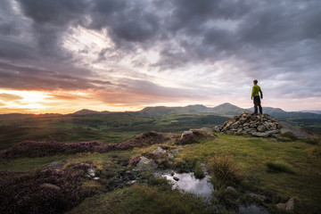 Strong hiker happy and enjoying sunset over Lake District England mountain background