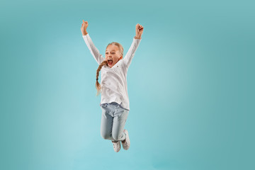 Adorable small child at blue studio. The girl is jumping and smiling. Young emotional surprised teen girl. Human emotions, facial expression concept.