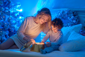 Young mother and her son are opening a Christmas gift box of shining light and magic. Happy family. Nativity night. Xmas holidays.