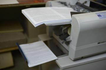 Фолдер складывает листы бумаги пополам