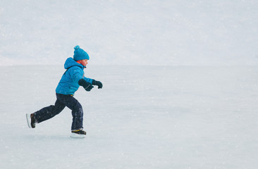 little boy skating on ice in winter nature