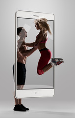 Athletic couple exercising, Strong muscular sportsman training with his fit girlfriend, concept virtual reality of the smartphone. going out of the device