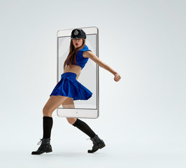 Portrait of young attractive woman dancing in police uniform, concept virtual reality of the smartphone. going out of the device