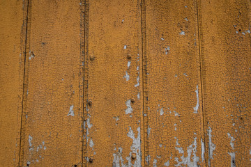 Weathered orange paint blistering off wooden plank background detail