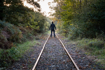 Strong male standing on old railroad track in the ardennes forest in autumn