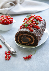 chocolate biscuit roll with berries on the table