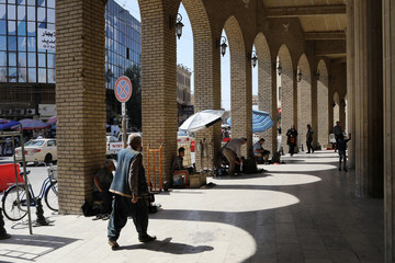 Kurdish people walk on a street at the old city of Erbil