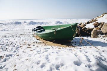 Green boat on a frozen beach