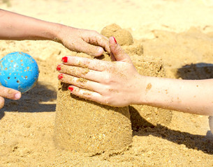 Closeup of a child hand, playing in the sand. Mother and kid making castles of sand at tropical beach and having fun.Joint activity concept