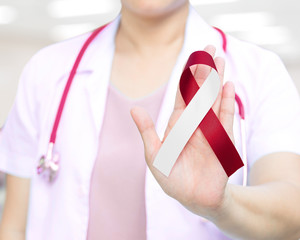 Red and white ribbon awareness in doctor's hand for Aplastic Anemia,Deep Vein Thrombosis (DVT),Head & Neck Cancer,Oral Cancer,Squamous Cell Carcinoma.