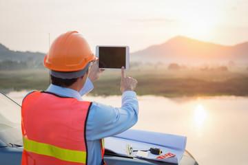 Surveyor engineer is measuring level on construction site.